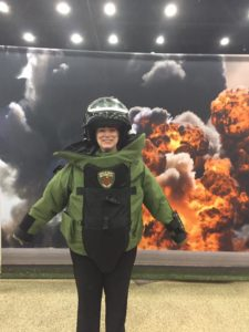 Rhonda in a bomb suit jacket and helmet in front of a explosion backdrop