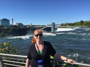 Rhonda stands at at a rail with Niagara Falls in the background.