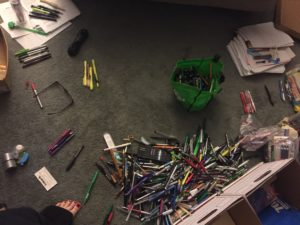 Aerial view of piles of unsorted ink pens and pencils.