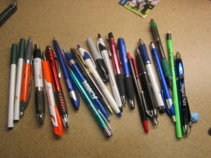 A collection of pens and pencils from various companies.